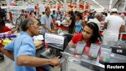 Un cliente coloca su dedo en un captahuellas para comprar productos en un supermercado estatal.