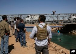 U.S. soldiers in civilian clothes, foreground, watch boys diving into a canal from a newly opened bridge, which had been destroyed last summer during fighting between U.S.-backed Syrian Democratic Forces fighters and Islamic State militants, in Raqqa, Syr