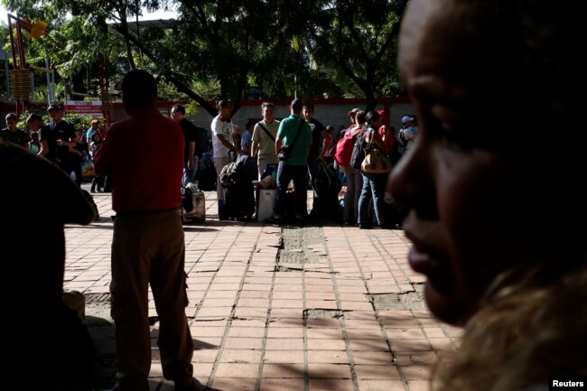 Personas que viajan en autobús desde Caracas a Ecuador hacen fila para sellar sus pasaportes en la oficina de control de migración en San Antonio del Táchira, Venezuela, el 8 de noviembre de 2017.