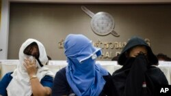 FILE - Unidentified Thai suspects of human trafficking appear at a news conference at police headquarters in Bangkok, Thailand, Aug. 4, 2015.