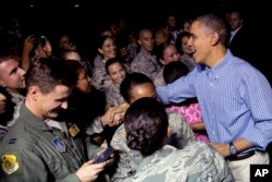 President Barack Obama greets members of the military as he arrives with the first family on Air Force One at Joint Base Pearl Harbor-Hickam, in Honolulu, Hawaii, Dec. 20, 2013.