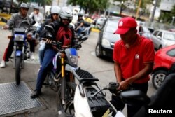 FILE - A worker pumps gas into a motorcycle as people wait in line to fill their vehicles' tanks at a state-owned PDVSA station in Caracas, Venezuela in March.
