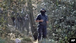 A state police stands guard at the site where at least 5 bodies were found in a clandestine grave on the outskirts of Mexico City, February 27, 2011
