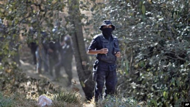 State police stand guard at the site where at least five bodies were found in a clandestine grave on the outskirts of Mexico City,  February 27, 2011
