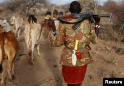FILE - A Turkana tribesman carries his gun in order to protect his cattle from rival Pokot and Samburu tribesmen near Baragoy, Kenya February 13, 2017.