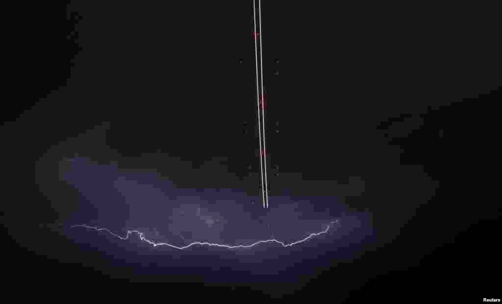 A jet aircraft takes off as lightning strikes across the sky during a monsoon storm at McCarran International Airport in Las Vegas, Nevada, USA, July 7, 2014.