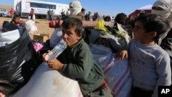 Refugiados sirios esperan ayuda en la frontera entre Siria y Turquía.