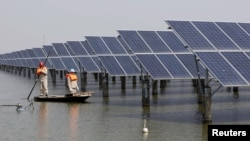 FILE - Employees examine solar panels installed at a pond in Lianyungang, Jiangsu Province, China, March 16, 2016. Efforts are underway to take the green financing agenda beyond clean energy projects.