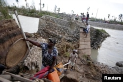 People use a handmade ladder after the bridge has been destroyed by Hurricane Matthew in Chantal, Haiti, Oct. 7, 2016.