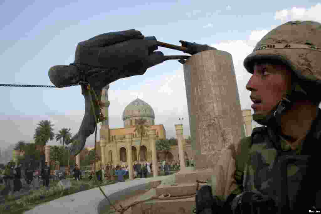 U.S. Marine Corp Assaultman Kirk Dalrymple watches as a statue of Iraq's President Saddam Hussein falls in central Baghdad, April 9, 2003.
