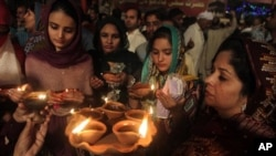 Sufi devotees carry clay oil lamps at a shrine of Madhu Lal Shah Hussain, a poet also regarded as a Sufi saint, during an annual festival to celebrate him in Lahore, Pakistan, Saturday, March 26, 2016. (AP Photo/K.M Chaudary)