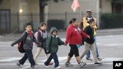Anak-anak sekolah menyeberang jalan menuju sekolah mereka di SMP Sam Tasby, Vickery Meadow, Dallas (Foto: dok). Anak-anak yang dikarantina karena Ebola, sudah mulai diperbolehkan kembali masuk sekolah, termasuk Ikeoluwa Opayemi (7 tahun), siswa di Milford, Connecticut (31/10).