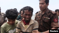 A member of Border Guards of Bangladesh comforts a Rohingya from Burma who was arrested while trying to get into Bangladesh, in Teknaf, June 18, 2012.