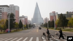 戴著口罩推車從北韓首都平壤柳京飯店前的一條路上走過。(2020年4月28日)