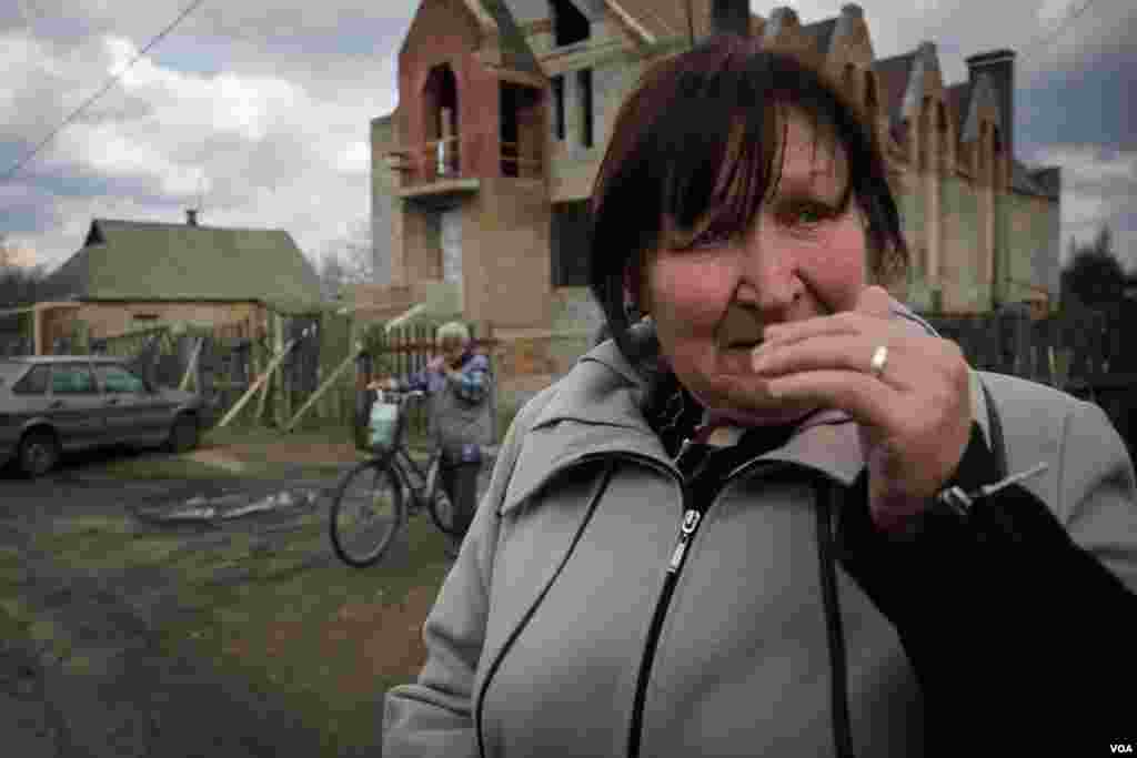 "Local resident Lida cries outside Noah's Ark Church in the town of Krasnohorivka, saying, ""in Kyiv they are far from reality, they cannot understand that war came to this town."" (Adam Bailes/VOA)"