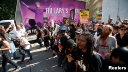 Protestors against police violence make their through the city pass an advertisement for a film featuring an image of Democratic Presidential Hillary Clinton near the Republican National Convention in Cleveland, Ohio, US, July 19, 2016.