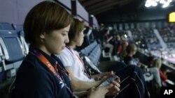 Atlet Jepang Miyuki Maeda dengan iPhone saat menonton pertandingan badminton pada Olimpiade London. (Foto: AP/Saurabh Das)