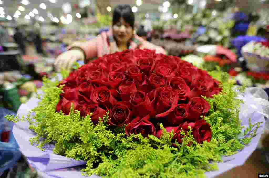 A woman packs a bouquet of 99 roses for the upcoming Valentine's Day at a market, in Beijing, China.