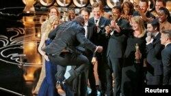 """Steve McQueen, sutradara dan produser """"12 Years A Slave"""", melompat di panggung saat menerima penghargaan film terbaik pada Academy Awards ke-86, disaksikan para aktor dan kru. (Reuters/Lucy Nicholson)"""