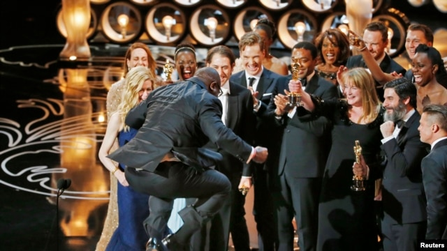 "Director and producer Steve McQueen jumps after accepting the Oscar for best picture for his work in ""12 Years a Slave"" at the 86th Academy Awards in Hollywood, CA, March 2, 2014."
