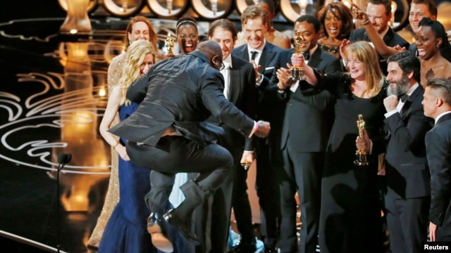 Director and producer Steve McQueen jumps after accepting the Oscar for best picture for his work in