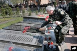 FILE - A Ukrainian lays flowers on the tombstone with his relative's name, during a requiem ceremony to commemorate victims of the Chernobyl tragedy, in Ukraine's capital Kiev, Ukraine, April 26, 2015.