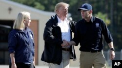 President Donald Trump shakes hands with FEMA Administrator Brock Long as Homeland Security Secretary Kirstjen Nielsen watches after visiting areas in North Carolina and South Carolina impacted by Hurricane Florence, Sept. 19, 2018, at Myrtle Beach International Airport in Myrtle Beach, S.C.