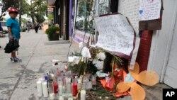 Un jeune garçon regarde des objets déposés en la mémoire d'Eric Garner, vendredi 1 août 2014, dans l'arrondissement de Staten Island dans l'Etat de New York.