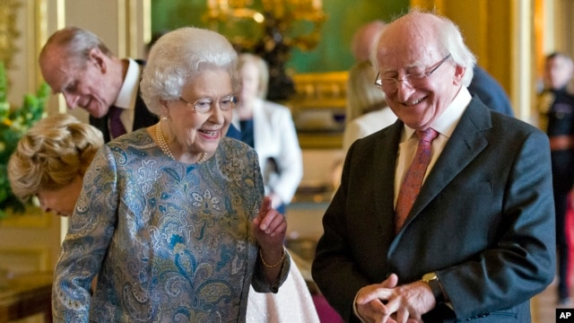 President of Ireland Michael D Higgins laughs with Britain's Queen Elizabeth II as they view items of Irish interest extracted from the Royal Collection and displayed in the Green Drawing Room at Windsor Castle, in Windsor, England, April 8, 2014.