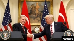 FILE - Turkey's President Recep Tayyip Erdogan, left, shakes hands with U.S President Donald Trump as they give statements to reporters in the Roosevelt Room of the White House in Washington, May 16, 2017.