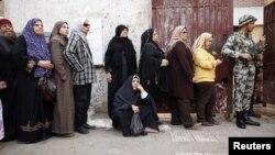 Mujeres hacen fila en El Cairo para votar en el referendo. Todos los centros de votación son custodiados por militares.