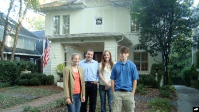 The Salwens in front of their smaller home after selling their mansion and donating half of the profits to charity.