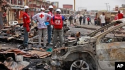 FILE - Red Cross personnel search for remains at the site of one of Tuesday's car bombs in Jos, Nigeria, May 21, 2014.