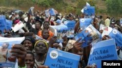 Parents, tuteurs et amis entonnent des chansons traditionnelles et portent des affiches pour la prévention du VIH/SIDA lors d'une cérémonie d'initiation masculine de l'adolescence à l'âge adulte dans le village de Njoloma, au Malawi, le 27 août 2006.