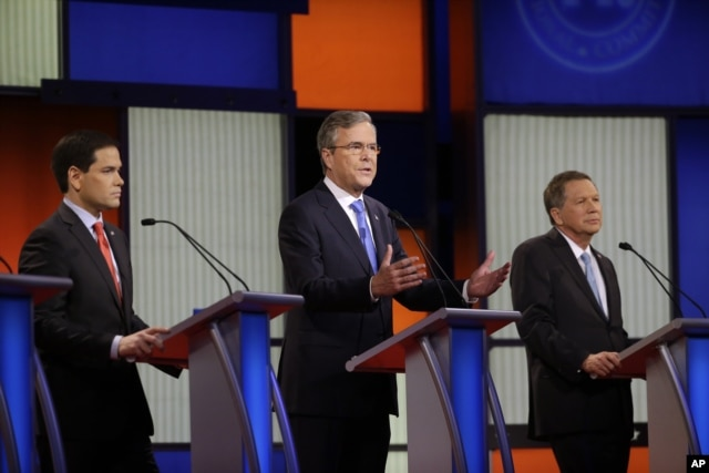 Jeb Bush, center, speaks as Marco Rubio, right and John Kasich listen during a Republican presidential primary debate in Des Moines, Iowa, Jan. 28, 2016.