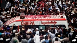 People throw rose petals on an ambulance carrying the body of Pakistani Sufi singer Amjad Sabri during his funeral in Karachi, Pakistan, June 23, 2016.
