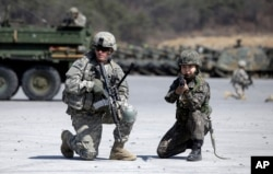 FILE - A U.S. Army soldier and a South Korean Army soldier take their position during joint military exercises between South Korea and the United States in Pocheon, north of Seoul, South Korea, March 25, 2015. China has proposed that the United States suspend joint military exercises with South Korea in exchange for North Korea putting on hold further nuclear and ballistic missile tests.