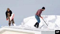 D.J. Schloss, left, and Doug Metz clear snow from a roof on Abbey Lane in Alden, N.Y., Nov. 20, 2014.