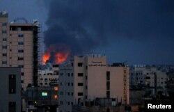 Asap dan api terlihat di atas gedung-gedung, di tengah meningkatnya pertempuran Israel-Palestina, di Gaza, 20 Mei 2021.