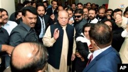 In this photo released by Pakistan Muslim League, Pakistani deposed Prime Minister Nawaz Sharif, center, arrives at an anti-corruption court in Islamabad, Pakistan, Tuesday, Sept. 26, 2017.