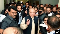 FILE - In this photo released by Pakistan Muslim League, Pakistani deposed Prime Minister Nawaz Sharif, center, arrives at an anti-corruption court in Islamabad, Pakistan, Sept. 26, 2017.