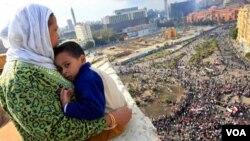 Una madre egipcia sostiene a su hijo en brazos mientras observa a los miles de manifestantes reunidos en la plaza Tahirir demandando la renuncia de Mubarak.