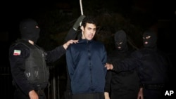 FILE - Iranian policemen prepare to hang a young convict in Tehran, Iran, Jan. 20, 2013.