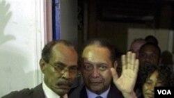 Ansyen diktatè ayisyen Jean-Claude Duvalier (nan mitan foto a) k ap salye patizan li depi balkon yon otèl kote li desann apre debakman li dimanch 16 janvye 2011 la nan peyi Dayiti apre 25 kan egzil