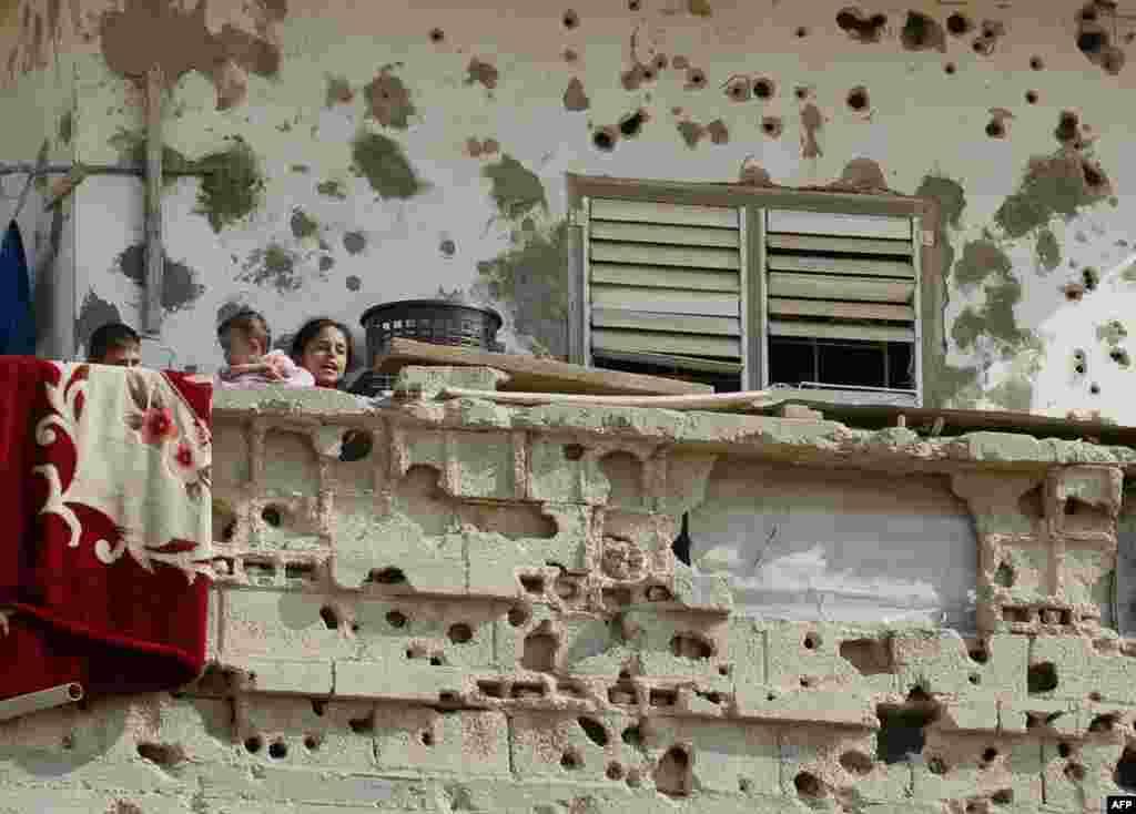 Palestinian children stand on the balcony of their family house which was damaged during an Israeli army operation launched after the killing of top Hamas military commander Ahmed Jaabari last year, in Rafah, southern Gaza Strip.