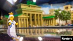 FILE - A Lego figure representing Britain's Queen Elizabeth II is placed in front of the Brandenburg Gate made of Lego bricks, in Legoland in Berlin, Germany, June 18, 2015. Lego has unveiled a new model in honor of the May 19 royal wedding of Prince Harry and Meghan Markle.