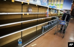 Shelves of bottles of water sit mostly empty at a supermarket in Atlanta, Jan. 6, 2017. Shoppers emptied shelves of bread and milk, and states of emergency were declared in Alabama, Georgia and the Carolinas ahead of a winter storm.