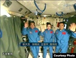 FILE - In this image taken June 20, 2013, and made from CCTV, Chinese astronauts from left, Zhang Xiaoguang, Wang Yaping and Nie Haisheng, wave during a live broadcast from onboard the Tiangong 1 prototype space station.