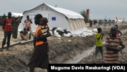 Children living at the UNMISS compound in Malakal hang around outdoors near a UNICEF tent. There are no schools at the UNMISS base, and the schools in town are shut.