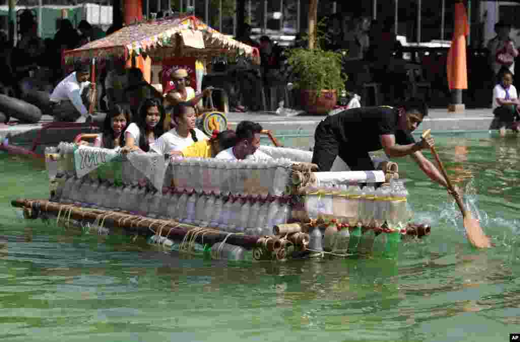 Filipinos paddle on a small boat they made with used plastic bottles and other recycled materials to join a boat-making competition in Manila, Philippines.